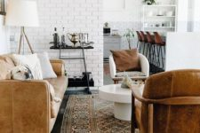 a stylish loft space with white brick walls, warm-colored wood and leather furniture and touches of gold