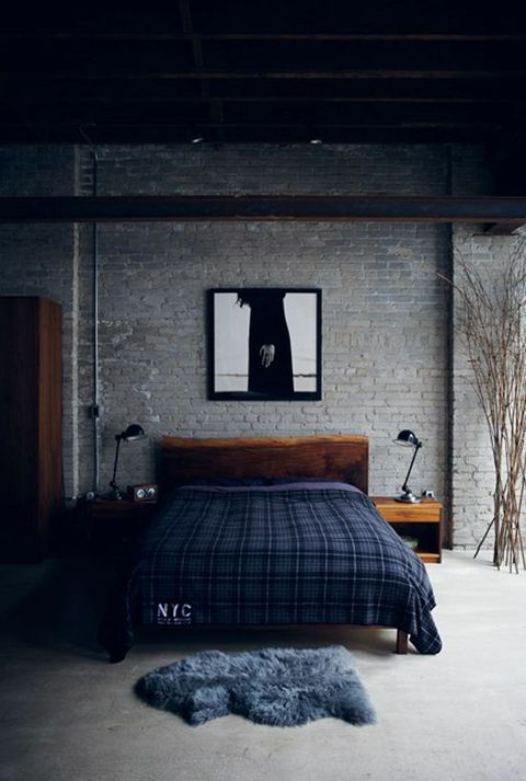 a stylish masculine industrial bedroom with brick walls, stained wooden furniture, plaid bedding and metal table lamps