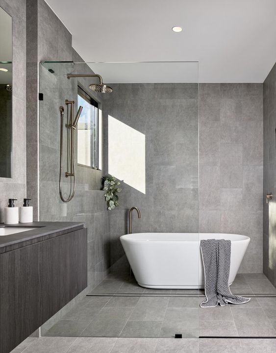 a stylish minimalist bathroom in grey, clad with tiles, with a floatign vanity and a free-standing bathtub