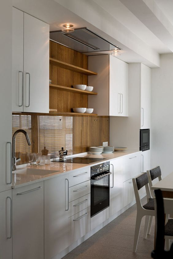 a stylish minimalist white kitchen with a wooden backsplash that is covered with sheer glass to make it more durable