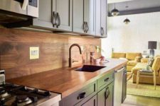 a stylish two tone kitchen in light blue and navy, with a wooden backsplash and countertops plus leather handles