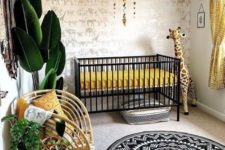 a super bold safari nursery with an animal print wall, a black crib with mustard bedding, a tassel chandelier, rattan furniture and potted plants plus a printed rug