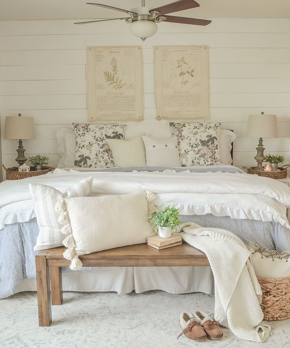 a sweet and chic farmhouse bedroom with pretty bedding, a wooden bench, baskets and vintage posters on the wall