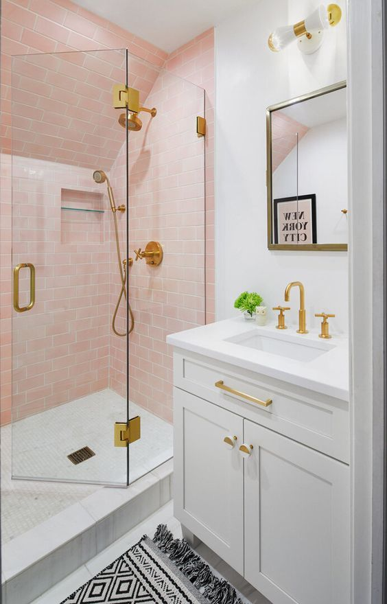 a sweet bathroom with light pink tiles in the shower, with white appliances and touches of gold to add elegance to the space