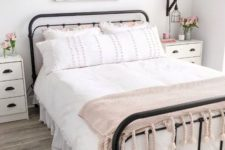 a sweet farmhouse bedroom with a forged bed, white nightstands, pink blooms and a sweet pink blanket