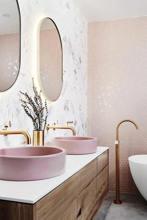 a tender bathroom with blush hexagon tiles, a matching sink, white marble tiles and touches of gold for chic