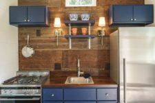 a tiny yet chic kkitchen with navy cabinets and a wooden backsplash wall plus a matching countertop is really cool