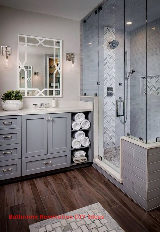 a traditional grey bathroom done with various tiles, a grey vanity with much storage space potted greenery and lots of lights