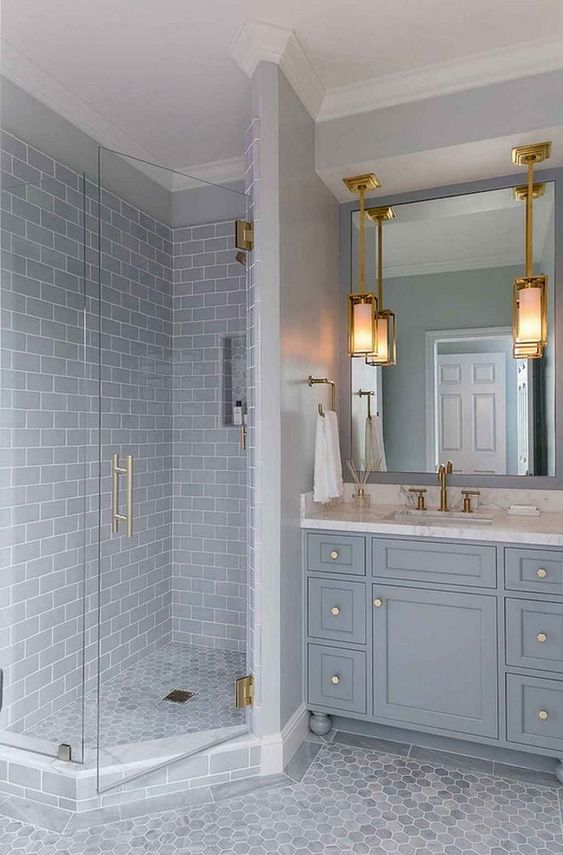 a traditional light colored grey bathroom with subway and hex tiles, with a traditional vanity and touches of gold