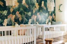 a tropical nursery with a trendy dark tropical leaf wall, boho chandeliers, painted stools and fun pillows