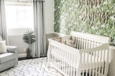 a tropical nursery with a tropical leaf wall, neutral furniture, a printed rug and some greenery