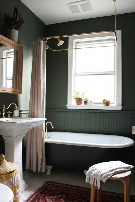 a vintage dark green bathroom clad with beadboard, a black tub, a free-standing sink, pastel textiles and touches of brass