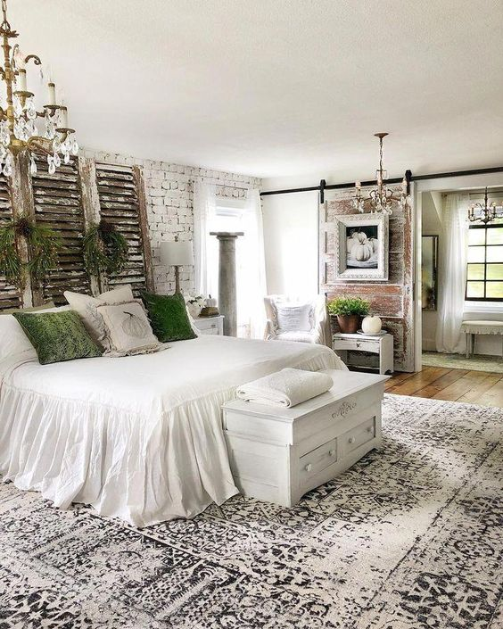 a vintage farmhouse bedroom with brick walls, reclaimed wood, shabby shutters, greenery and green pillows plus vintage chandeliers
