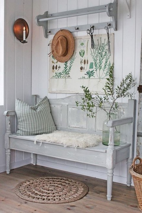 a vintage farmhouse entryway with a whitewashed bench, rack, an artwork, a straw hat and a candle lamp