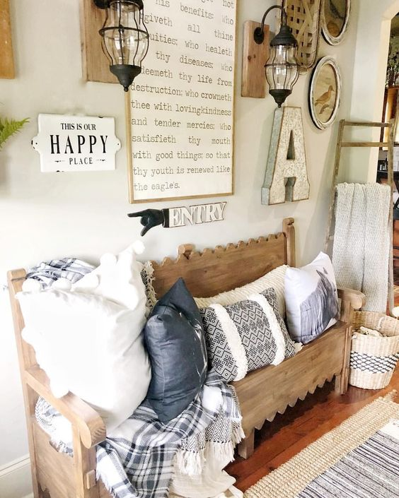 a vintage farmhouse entryway with wall lanterns, a carved wooden bench, lot sof pillows and some artworks on the wall