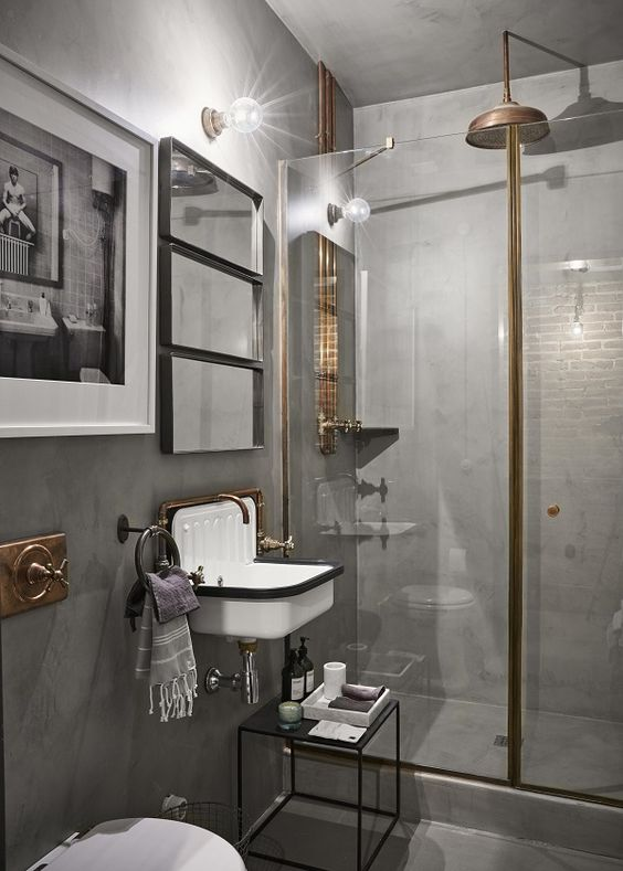 a vintage industrial bathroom with concrete walls and a floor, with brass and gold fixtures, a vintage metal sink and mirrors plus a small stool