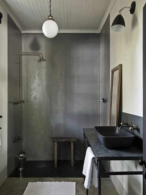 a vintage industrial bathroom with shower walls of concrete, a black vanity and a black sink plus vintage fixtures