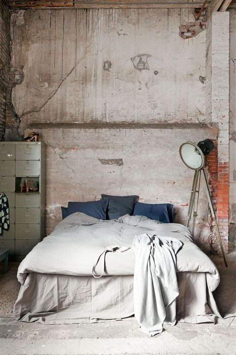 a vintage industrial bedroom with shabby chic brick walls, a floor lamp, a metal cabinet for storage and a concrete floor