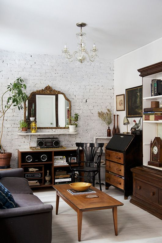 a vintage-inspired living room with white brick walls, chic refined furniture and accessories and potted greenery