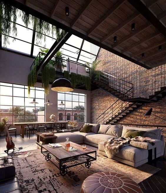 a welcoming and airy living room in industrial style, with brick walls, a metal and wood table, a leather ottoman and an L-shaped sofa plus greenery