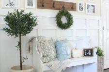 a welcoming farmhouse entryway with a gallery wall of family pics, a white bench with pillows, potted plants and a rack