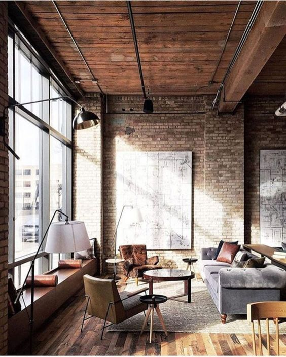 a welcoming industrial living room with brick walls, a wooden ceiling, metal beams and lamps, cozy retro furniture and rugs