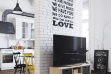 a white brick wall that adds interest and texture to the space dividing the open layout at the same time