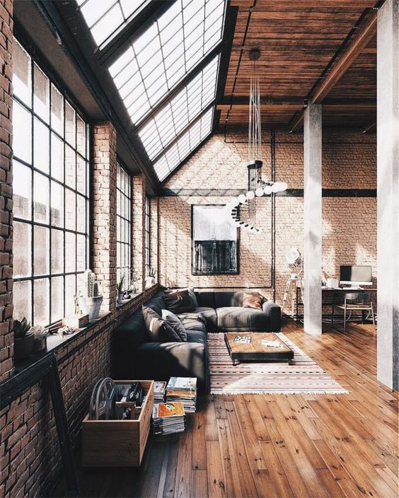 an airy industrial living room with windows and skylights, brick walls, a wooden ceiling, comfy furniture and a catchy chandelier