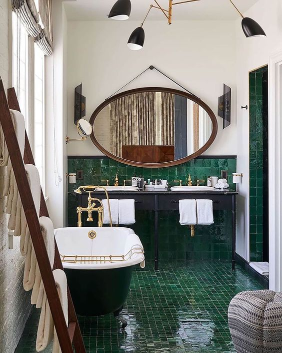 an art deco bathroom clad with emerald tiles, a green tub, a grey vanity and a large mirror in a copper frame
