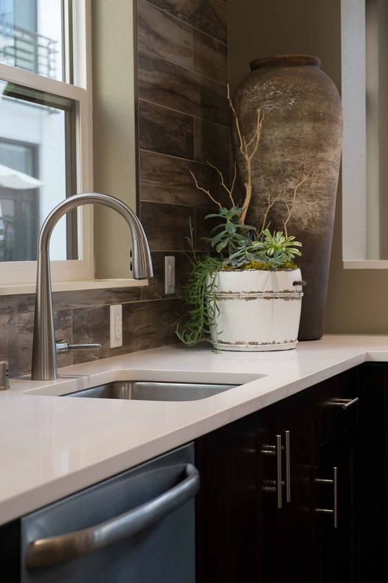an elegant black kitchen with white countertops and a wooden backsplash wall looks chic, bold and unusual
