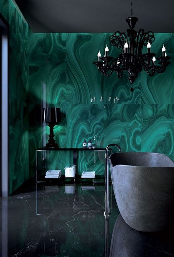 an exquisite bathroom done with catchy dark grene tiles, a grey stone tub, a black chandelier and a black table