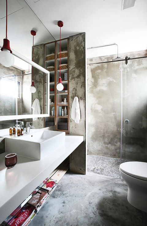 an industrial bathroom done of concrete, with a white floating vanity, red bulbs, a large lit up mirror