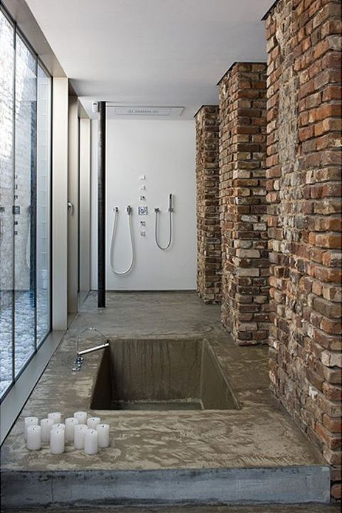 an industrial bathroom with a concrete floor and a built in tub, brick pillar and a glazed wall plus candles
