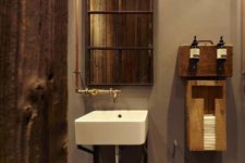 an industrial bathroom with concrete walls, a basket, exposed piping and reclaimed wood here and there