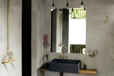 an industrial bathroom with concrete walls and a floor, with hanging bulbs, brass and gold fixtures and a floating vanity