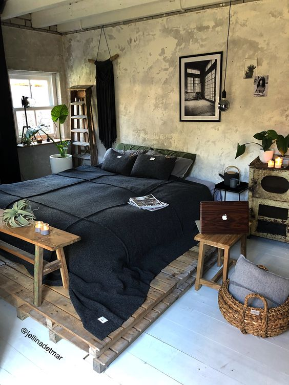 an industrial bedorom with shabby chic walls, a pallet bed, simple wooden furniture and dark bedding