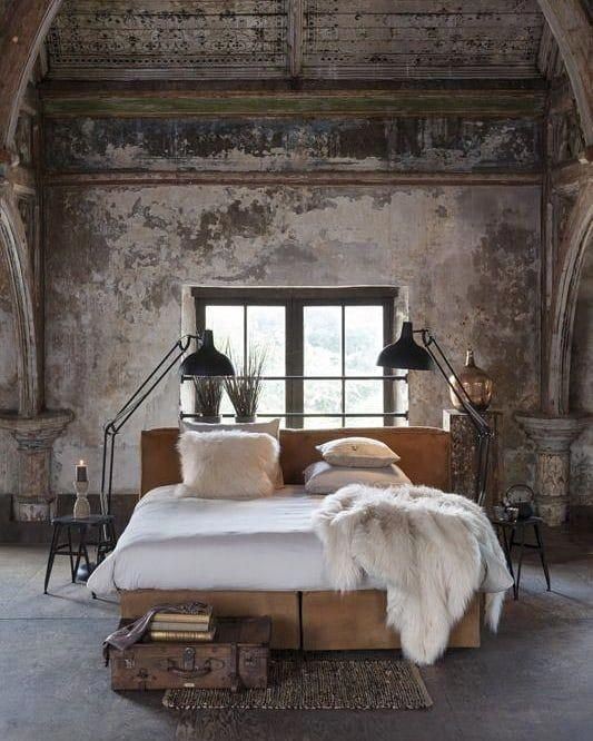 an industrial bedroom with shabby chic walls, a wooden ceiling, a concrete floor and upholstered bed, metal floor lamps and a vintage suitcase