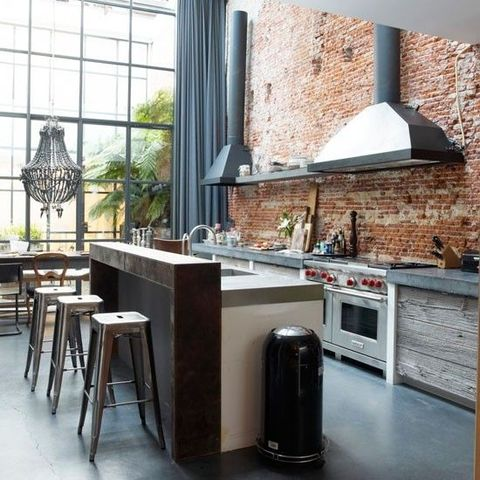 an industrial kitchen with a red brick wall, metal hoods and appliances, a kitchen island with a concrete and wooden top