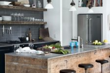 an industrial kitchen with grey tiles, black metal cabinets and a concrete countertop, a rough wooden kitchen island and rough shelves