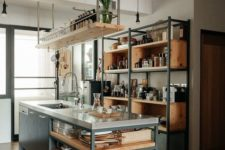 an industrial kitchen with open storage units with blakc metal framing, exposed pipes and a large kitchen island