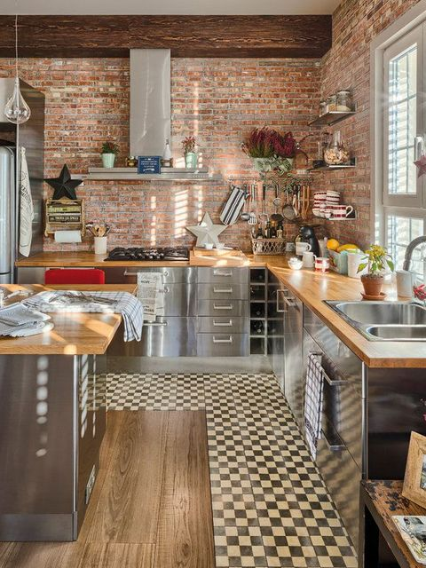 an industrial kitchen with polished metal cabinets, wooden countertops, brick walls, bulbs and a mosaic tile floor