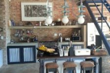 an industrial kitchen with red brick walls, concrete cabinets, vintage lamps, a vintage kitchen island