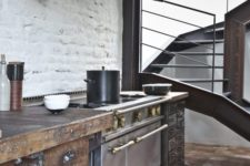 an industrial kitchen with rough wooden cabinets, metal appliances, a tile clad hood and vintage lamps