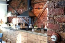 an industrial kitchen with rough wooden furniture with concrete countertops, brick walls, a black hood, mismatching furniture
