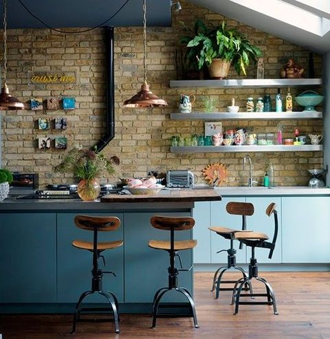 an industrial kitchen with sleek blue cabinets, metal countertops, a brick wall, extended piping and copper lamps
