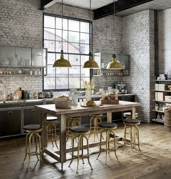an industrial kitchen with white brick walls, dark plywood cabinets, a wooden table and vintage stools plus vintage lamps
