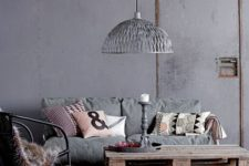 an industrial minimalist living room with concrete walls, a wooden floor, metal and wood furniture, a metal pendant lamp