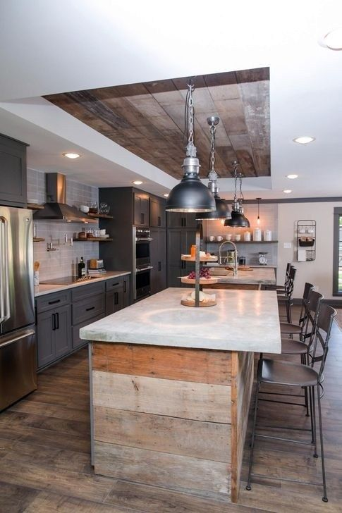 an industrial space with a reclaimed wooden ceiling and kitchen islands, grey cabinets and vintage lamps