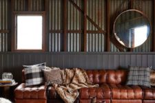 an industrial space with corrugated steel walls, a wooden ceiling, metal lamps and a table, an animal rug and a leather sofa