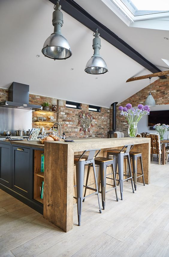 an industrial space with graphite grey cabinets, a wooden kitchen island, metal stools, lamps and a skylight
